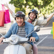 Happy mature couple riding a scooter in the city — Stock Photo #51602413