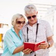 Happy tourist couple using tour guide book in the city — Stock Photo #51602431