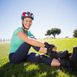 Fit mature woman tying her roller blades on the grass — Stock Photo #51604587
