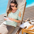 Woman reading book by pool with breakfast on table — Stock Photo #51605237