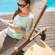 Woman reading book by swimming pool with champagne on table — Stock Photo #51605285