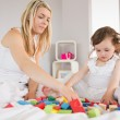 Mother and daughter playing with building blocks on bed — Stock Photo #51605359