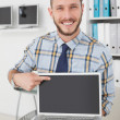 Happy casual businessman pointing to laptop — Stock Photo #51605383