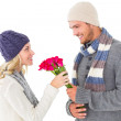 Attractive man in winter fashion offering roses to girlfriend — Stock Photo #51605469