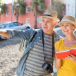 Happy tourist couple using guide book in the city — Stock Photo #51606073