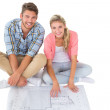 Attractive young couple sitting looking at blueprint — Stock Photo #51606857