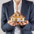 Businesswoman holding miniature model house — Stock Photo #51607637