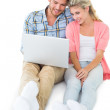 Attractive young couple sitting using laptop — Stock Photo #51607661