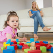 Girl playing with building blocks while mother on conch — Stock Photo #51608039