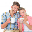 Attractive young couple sitting holding mugs — Stock Photo #51608173