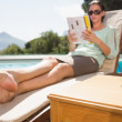 Woman reading book by pool with champagne in foreground — Stock Photo #51609425