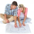 Attractive young couple sitting looking at blueprint — Stock Photo #51609757