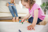 Girl drawing in the living room with mother sitting behind — Stock Photo