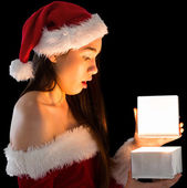 Brunette in santa outfit opening a gift — Stock Photo
