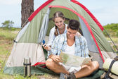 Couple looking at map outside their tent — Foto de Stock