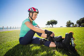 Fit mature woman tying her roller blades on the grass — Stock Photo