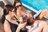 Women with drinks by swimming pool — Stock Photo