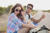 Couple hitchhiking on countryside road — Stock Photo