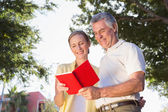 Happy senior couple using the guidebook  — Stock Photo