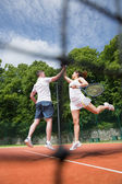 Tennis doubles team celebrating a win — Stock Photo