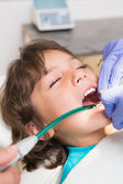 Pediatric dentist examining a little boys teeth in the dentists  — Stok fotoğraf