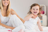 Mother and daughter sitting on bed at home — Foto Stock