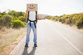 Man with smiley face hitchhiking on countryside road — Stock Photo