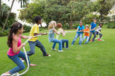 Pupils playing tug of war on the grass — Stok fotoğraf