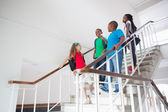 Cute pupils walking down stairs — Stock Photo