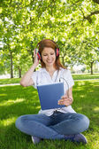 Redhead using her tablet pc — Stock Photo