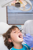 Pediatric dentist examining a little boys teeth in the dentists  — ストック写真