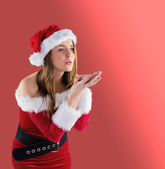 Brunette in santa outfit blowing over hands — Stock Photo
