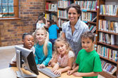 Pupils and teacher looking at computer in library — Stock Photo