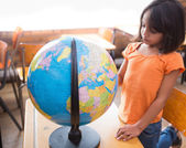 Little pupil looking at globe in classroom — Stock Photo