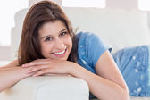 Pretty brunette smiling at camera on the couch — Stock fotografie