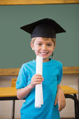 Pupil in mortar board in classroom — Stock Photo