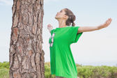 Female environmental activist in front of tree trunk — Stock Photo