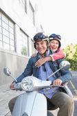 Happy senior couple riding a moped  — Stock Photo