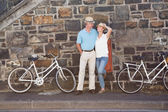 Happy senior couple going for a bike ride in the city — Stok fotoğraf
