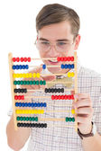 Nerdy hipster adding on abacus  — Stock Photo