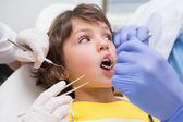 Dentist examining boys teeth — Stock Photo
