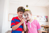 Pupils looking through magnifying glass — Stock Photo