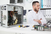 Computer engineer sitting with broken console — Stockfoto