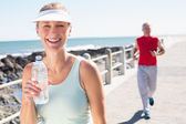 Fit mature couple jogging together on the pier — Stock Photo