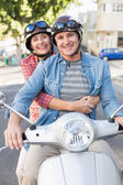 Happy mature couple riding a scooter in the city — Stock Photo
