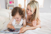 Mother and daughter using digital tablet on bed — Stock Photo