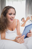 Happy woman using digital tablet in bed with man in background — Stock fotografie