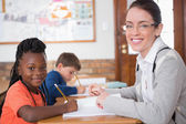 Pupil getting help from teacher in classroom — Stock Photo
