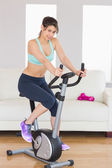 Fit brunette working out on exercise bike — Stock Photo