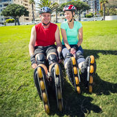Fit mature couple wearing roller blades on the grass — Stock Photo